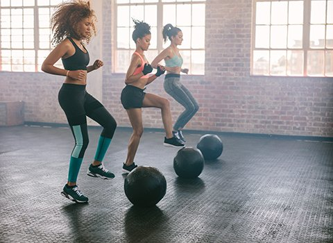 Three women exercising with medicine balls