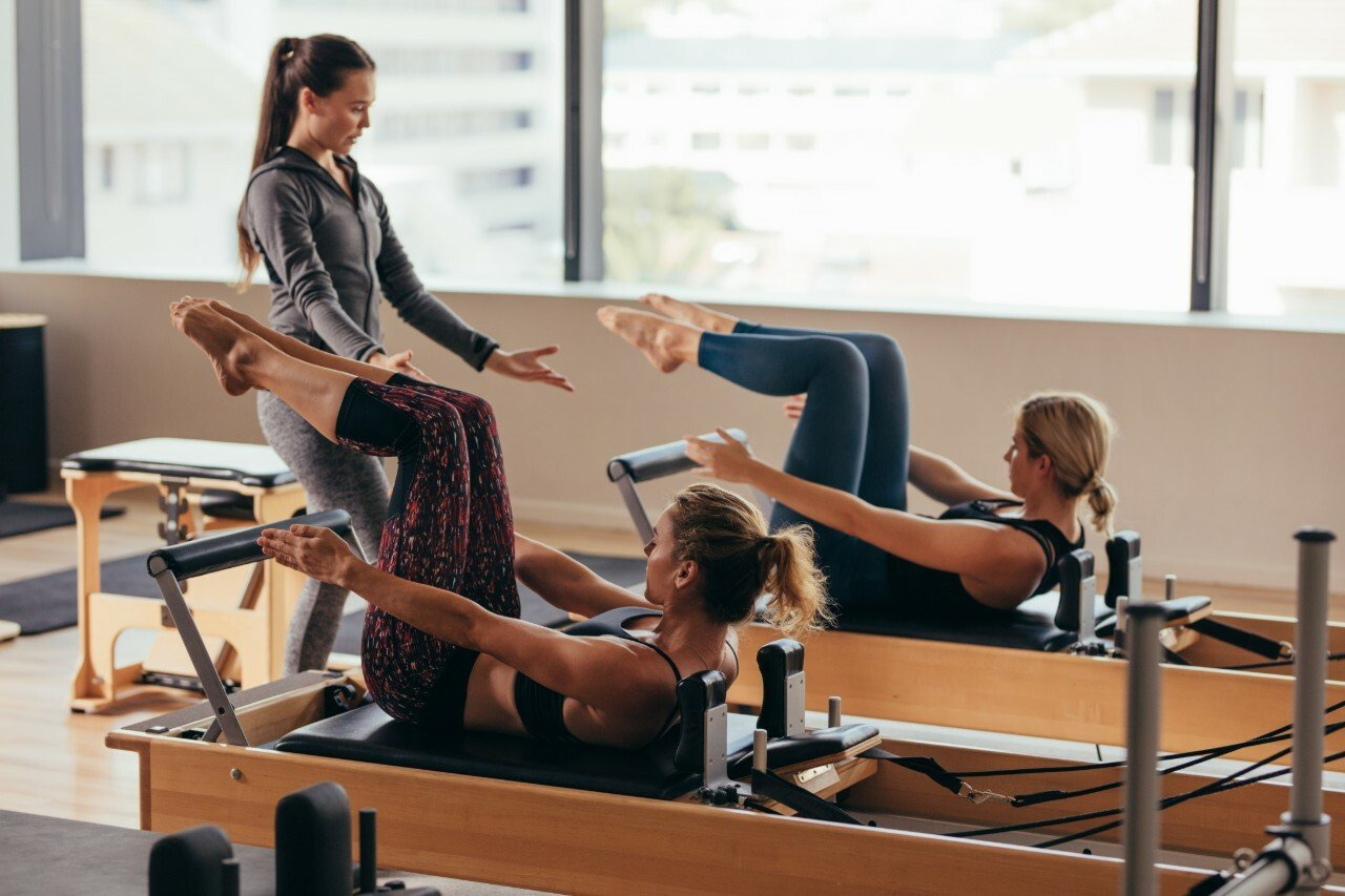 Two women doing reformer pilates with instructor