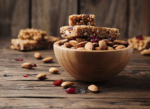Protein bars and almonds in a wooden bowl