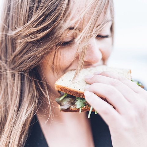 Close up of woman eating sandwich